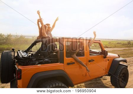 Group of friends having fun during road trip in a car