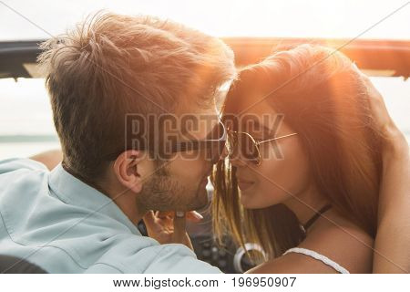 Close up of a smiling young couple kissing while sitting in a car