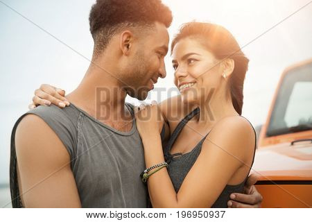 Close up of a beautiful young couple in love hugging and looking at each other outdoors