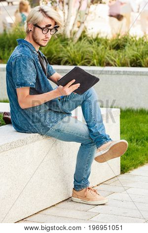 Male fashion technology student concept. Guy with tablet wearing jeans outfit and eccentric sunglasses sitting on white ledge