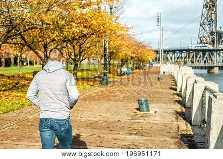 Man walking along the riverwalk in Portland city at autumn, Oregon, USA.