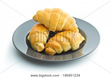 Tasty buttery croissants on plate isolated on white background.