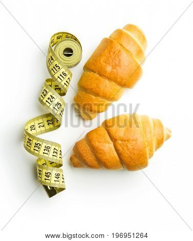 Tasty buttery croissants and measuring tape isolated on white background.