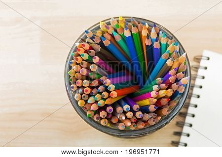 Top view of big glass full of coloring colored pencils with blurred sketch drawing book on wooden background