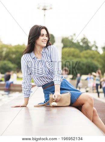 Young beautiful girl sitting by the city fountain in a blue shirt and skirt