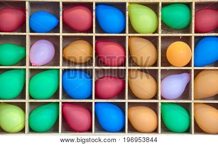 colorful inflated balloons in wooden boxes for carnival game