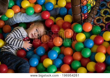 Young boy having fun and hiding in hundreds of colorful plastic balls