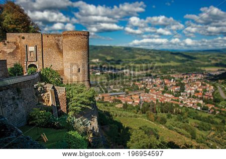 Overview of stone tower, green hill, vineyards and rooftops near a road at the city of Orvieto, an ancient, pleasant and well preserved medieval town. Located in Umbria, central Italy. Retouched photo