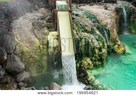 Mineral water from hot spring flowing over wooden box in Kusatsu Japan