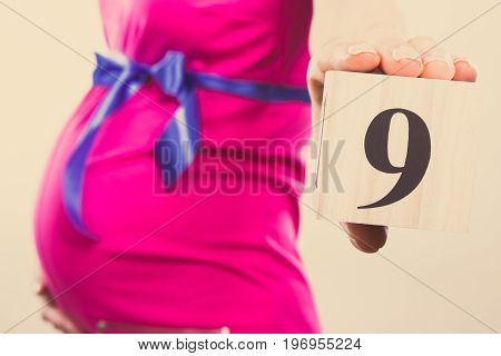 Vintage Photo, Hand Of Woman In Pregnant Showing Number Of Ninth Month Of Pregnancy, Expecting For B