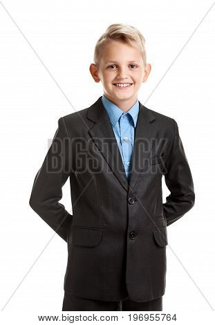 Portrait of confident schoolboy in suit holding hands behind back