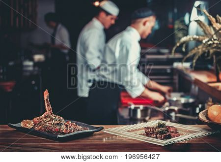 Food concept. Ready grilled pork ribs dish and beef steak with herbs. Ready to serve. Ready to eat. Two chefs working in the background interior of modern professional restaurant kitchen