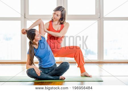 Two young woman in colorful sportswear making stretching exercises sitting on yoga mat. Thai massage element. Treatment, rest, relaxation, health care, spa. Big windows soft light in the background