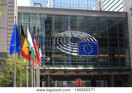 Brussels, Belgium - July 17, 2017: European Parliament building on a sunny day. Emblem of the European Parliament and EU countries flags.