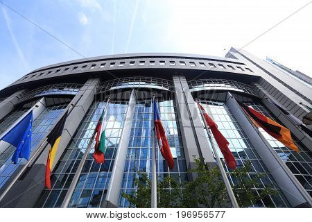 Brussels, Belgium - July 17, 2017: Flags on European Parliament building background. Flags of EU countries opposite facade of European Parliament building.