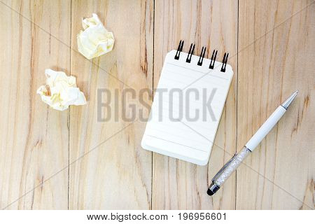 Small note book paper (notepad) for writing information with pen and crumpled paper balls on wooden table. view from above