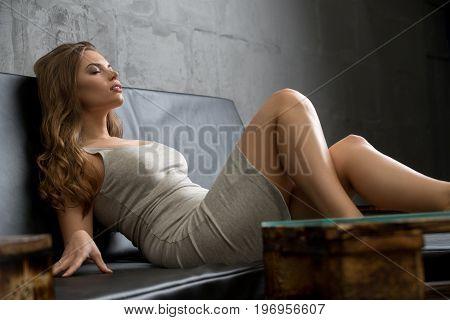 Pretty brunette wearing sexy beige dress relaxing on wooden sofa studio shot