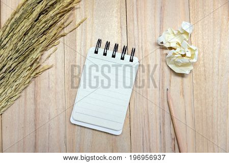 Small note book paper (notepad) for writing information with pencil and crumpled paper balls on wooden table. view from above