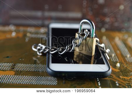 Data Security Encryption Protection Concept with Metallic Padlock chained over smartphone on electronic circuit board background.