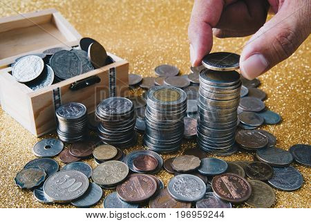 Hand putting a coin on stack of coins. Golden glittering background pile of coins in small wooden chest with coins from various countries scattering around.