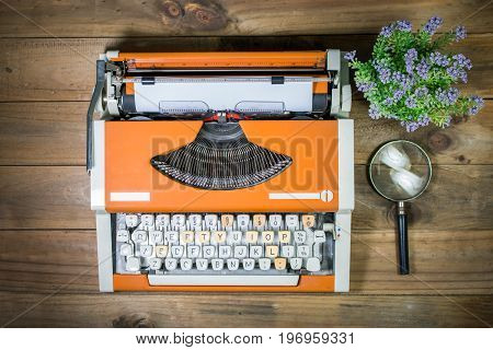 typewriter on wooden background with flower and magnifying glass | top view of typewriter