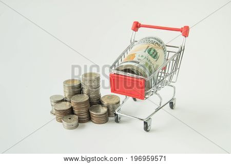 Stack of coins on white background in order of level from low to high with dollar banknote in mini supermarket trolley.