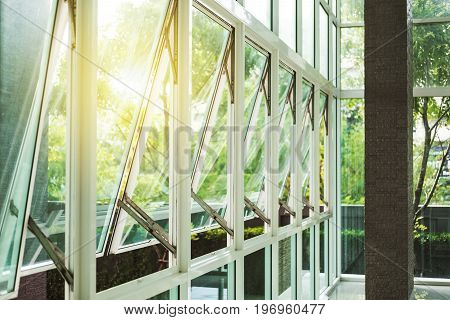 Modern office building wall and opened window in the morning, with bright sunlight