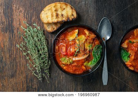 Two bowl of Italian soup minestrone with seasonal vegetables on rustic wooden table with copy space top view