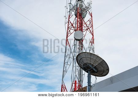 Telecommunication tower with satellite dish, on blue sky