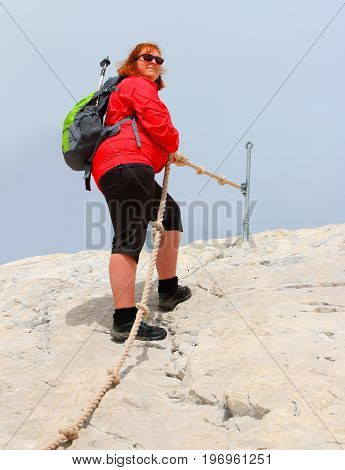 Overweight hiker woman on the top of snowy peak. Zugspitze arena, Germany. Active people enjoying outdoor sports in mountain landscape. Healthy lifestyle and slimming concept.