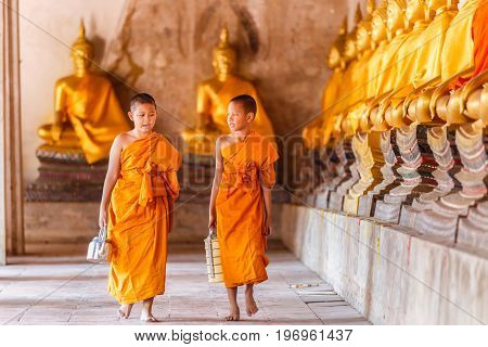 Two novices monk walking and talking in old temple at sunset time Ayutthaya Province Thailand