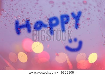 Rain drops and the word happy write on window with light bokeh rainy season abstract background.