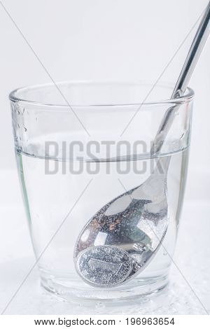 Japanese coin (yen) is picking up by silver spoon from a glass of water isolated on white background financial concept.
