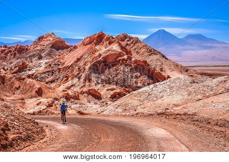 Female cyclist traveling on the road through the famous Valle the la Luna near San Pedro de Atacama, Chile, South America
