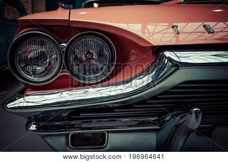 BERLIN - MAY 10 2015: Headlamp of a large personal luxury car Ford Thunderbird 390 Coupe (second generation) 1964. Stylization. Vintage toning. 28th Berlin-Brandenburg Oldtimer Day