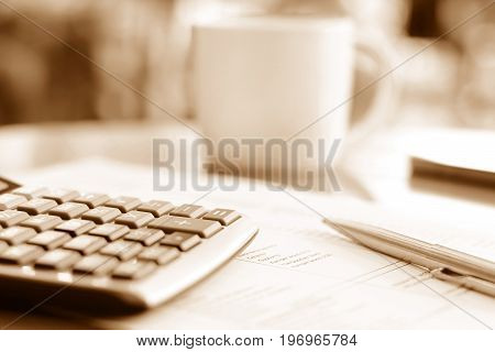 Calculator & pen over paper on the table with blur coffee cup background in brown sepia effect - soft focus