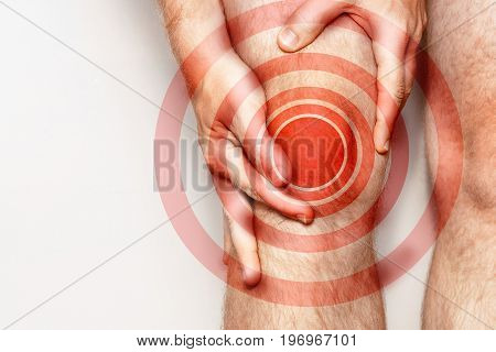 Acute pain in a knee joint close-up. Color image isolated on a white background. Pain area of red color.