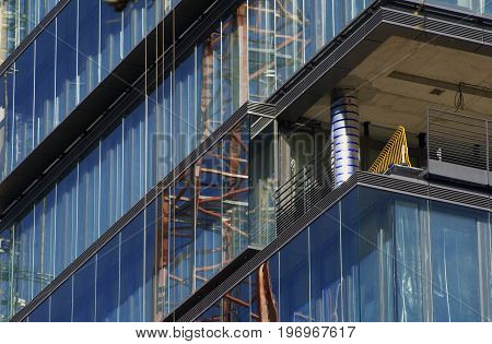the reflection of a crane in the glass facade of a building