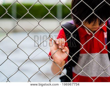 Portrait sad boy behind fence mesh netting. Emotions concept - sadness sorrow melancholy.