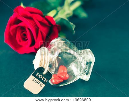Retro red heart in shape bottle with red rose background. LOVE and valentine's day concept.