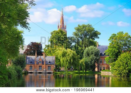 Cityscape of Bruges on a summer day. Old buildings and green trees on a water canal in Bruges.
