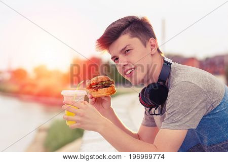 picture was taken on a sunny day а young guy is resting and eating a burger at sunset.