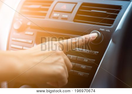 Passenger finger pushing button of car audio stereo player. Safety driver
