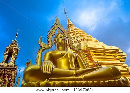Golden buddha statue with golden pagoda background , At Wat Phra That Doi Suthep temple is tourist attraction of Chiang Mai, Thailand.Focus at face of buddha statue.
