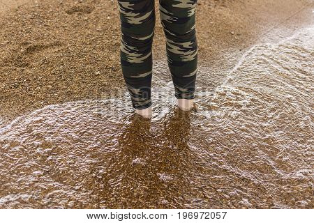 Feet in water at beach. legs walking in water