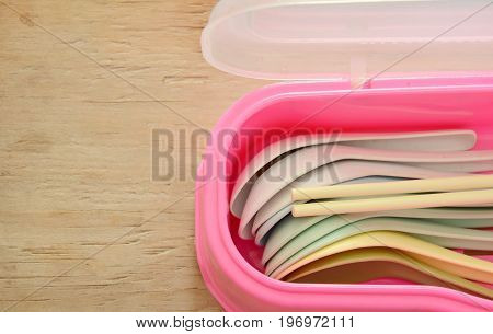 colorful plastic soup spoon and chopsticks in pink box