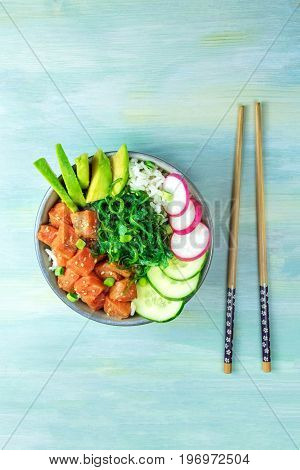 An overhead photo of poke, traditional Hawaiian raw fish salad, with chopsticks and copy space, on a teal blue background texture