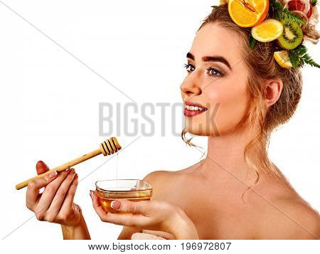 Honey facial mask with fresh fruits for hair and skin on woman head. Face of girl with beautiful face hold honeycombs for homemade organic skin and hair therapy. Natural cosmetics based on bee honey.