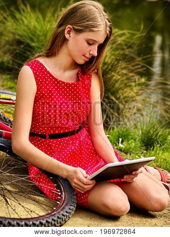 Bikes cycling girl wearing red polka dots dress recreation near bicycle into park. Children watch tablet pc in ecotourism. Female went into social network in campaign. Dependence on social networks.