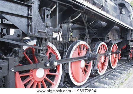 Photo of old steam locomotive wheels closeup.